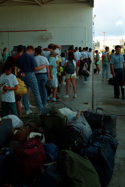 Evacuees from Naval Station, Subic Bay and Naval Air Station, Cubi Point stand in line for processing en route to the United States. Civilian and military personnel and their dependents are being evacuated from the Philippines in the aftermath of Mount Pinatubo's eruption as part of Operation FIERY VIGIL.