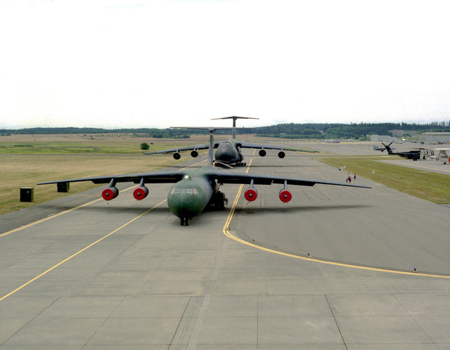 A C-141B Starlifter and a C-5 Galaxy, U.S. Air Force transport aircraft, are exhibited on a runway at the naval station's air show. Exact Date Shot Unknown