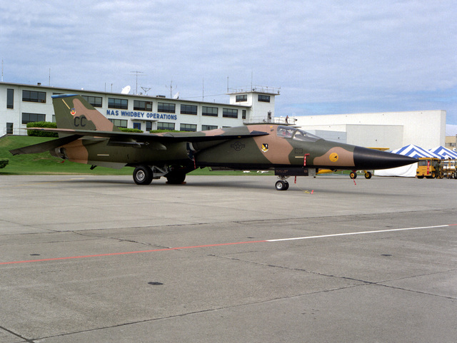 A U.S. Air Force F-111 aircraft of the 27th Tactical Fighter Wing is exhibited in front of the naval air station's operations building during an air show