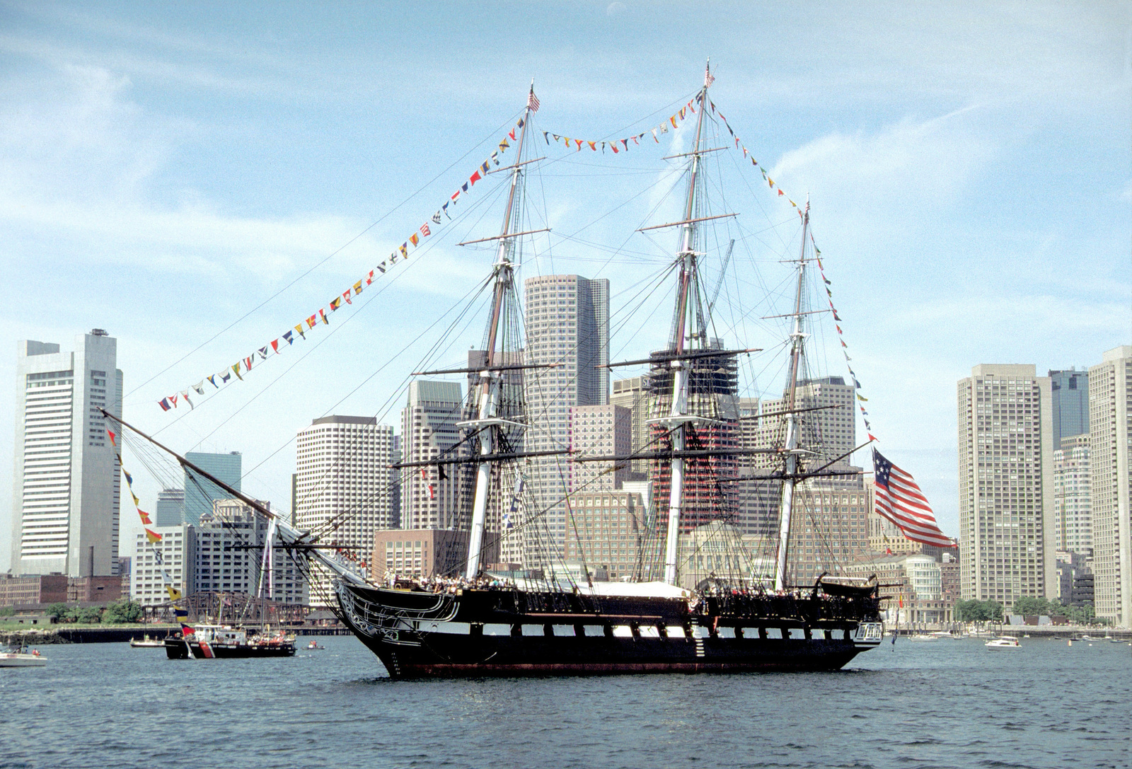 Guests fill the deck of the sail frigate USS CONSTITUTION during its annual turnaround cruise. The CONSTITUTION is towed into the harbor each year and returned to its berth facing the opposite direction so that its masts do not bend from the effects of the sun and wind
