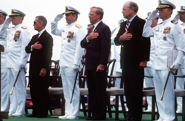 Officers and guests honor the flag during the commissioning ceremony of the guided missile destroyer USS ARLEIGH BURKE (DDG-51). They include, from left to right: Adm. Leon A. Edney, commander-in-chief, U.S. Atlantic Fleet/Supreme Allied Commander, Atlantic; H. Ross Perot, honorary commissioning foundation chairman; Adm. David E. Jeremiah, vice chairman, Joint Chiefs of STAFF; H. Lawrence Garrett III, secretary of the Navy; Richard B. Cheney, secretary of defense, and CMDR. John G. Morgan Jr., commanding officer of the BURKE
