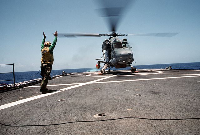 The landing signal enlisted man (LSE) aboard the destroyer USS O'BANNON (DD 987) signals to the pilot of an SH-2F Seasprite helicopter from Light Helicopter Anti-submarine Squadron 34 (HSL-34). The O'BANNON is sailing south to take part in UNITAS XXXII, a combined exercise involving the naval forces of the United States and nine South American nations