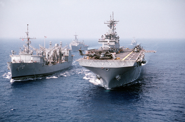 The replenishment oiler USS MILWAUKEE (AOR 2), left, conducts an underway replenishment with the amphibious assault ship USS WASP (LHD 1). In the background are the amphibious transport dock USS PONCE (LPD 15), left, and the tank landing ship USS SUMTER (LST 1181), right