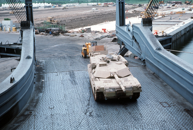 An M-1A1 Abrams main battle tank waits on the stern ramp of the Military Sealift Command-chartered vehicle cargo ship CAPE HUDSON (T-AKR-5066) as a trailer is pulled down the ramp by a forklift. The CAPE HUDSON transported the vehicles and other equipment back from the Persian Gulf region, where they were used in Operation Desert Shield and Operation Desert Storm