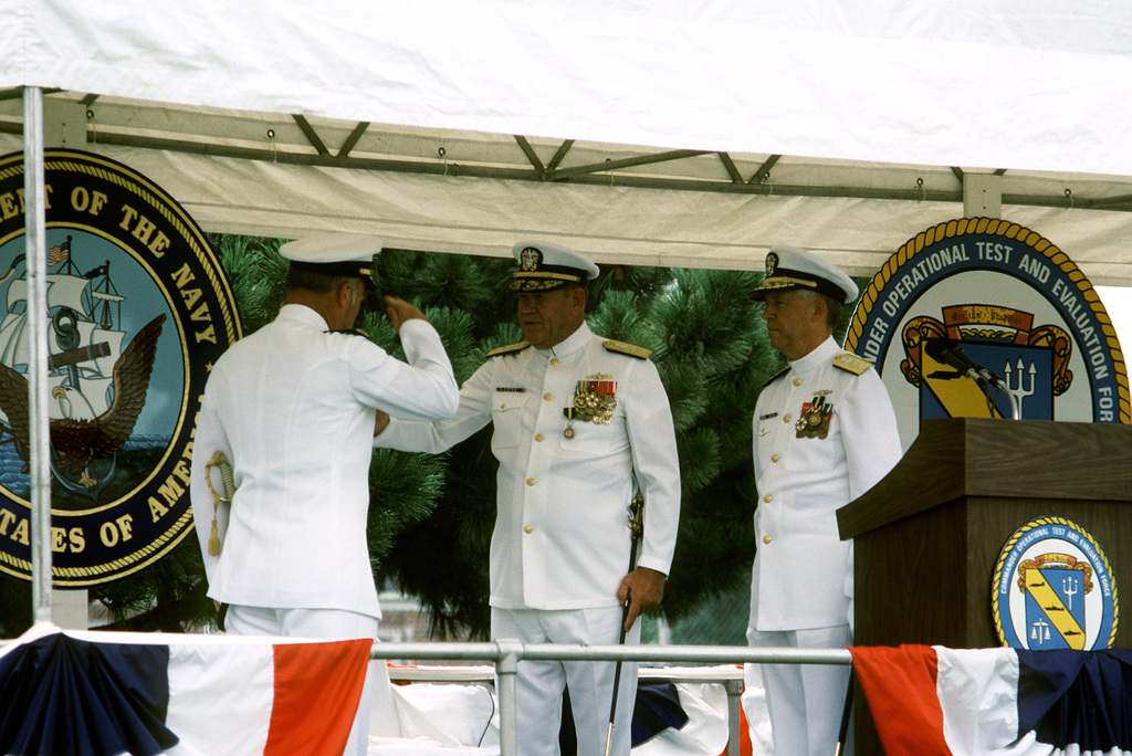 ADM Frank B. Kelso II returns the salute of RADM Hugh L. Webster, outgoing commander of the Operational Test and Evaluation Force, at the change of command ceremony during which Webster relinquished command to RADM Virgil L. Hill Jr., standing at podium