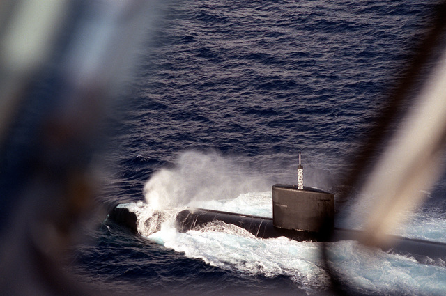 Spray blows back from the bow of the nuclear-powered attack submarine USS ALEXANDRIA (SSN-757) as the submarine operates off Andros Island, Bahamas, during post-commissioning trials. The ALEXANDRIA was commissioned on June 29, 1991.