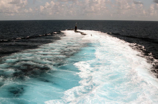 The nuclear-powered attack submarine USS ALEXANDRIA (SSN-757) begins a turn to port while operating off Andros Island, Bahamas, during post-commissioning trials. The ALEXANDRIA was commissioned on June 29, 1991.