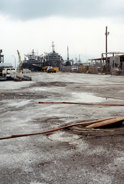 Ash and mud remain in some spots on the pier after a cleanup of the volcanic ash that fell on the base during the eruption of Mount Pinatubo. The fleet oiler USNS PONCHATOULA (T-AO-148), are in the background