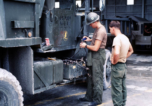 A Seabee cleans battery cables while performing preventive maintenance on a dump truck. Several Seabee units are at the air station to aid in the cleanup of the volcanic ash that fell during the eruption of Mount Pinatubo