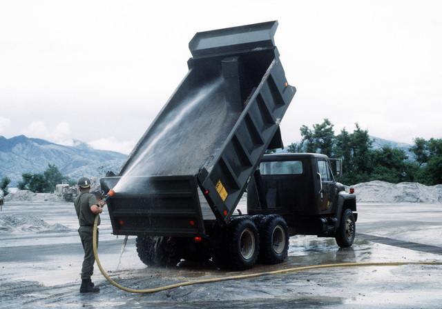A Seabee hoses out the bed of a dump truck that is being used in the cleanup of the volcanic ash that fell during the eruption of Mount Pinatubo