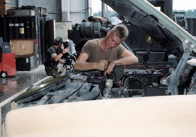 A Seabee performs preventive maintenance on a truck while Photographer's Mate 2nd Class Chaterine T. Hogan videotapes other Seabees at work in the background. Several Seabee units are at the air station to aid in the cleanup of the volcanic ash that fell during the eruption of Mount Pinatubo