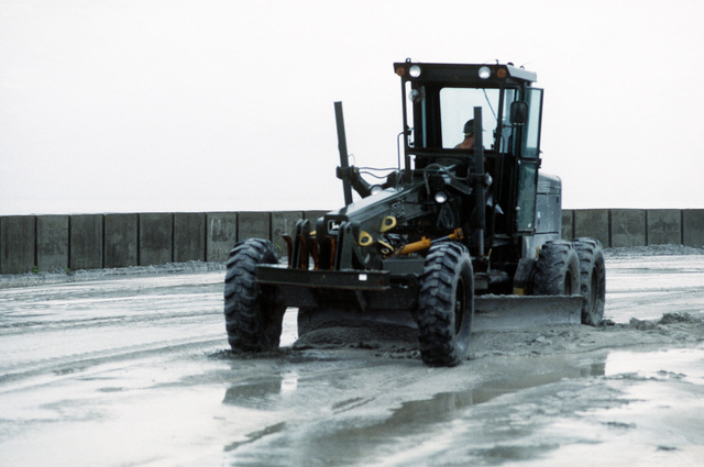 A Seabee uses a John Deere 670A motor grader to clear volcanic ash and mud from a road following the eruption of Mount Pinatubo