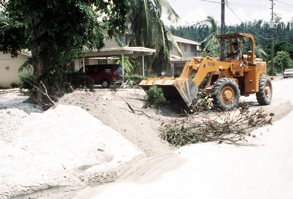 A worker uses a loader to remove ash and debris from yards in the aftermath of Mount Pinatubo's eruption. The volcano erupted for the first time in over 600 years on June 10th and covered the area in ash and debris