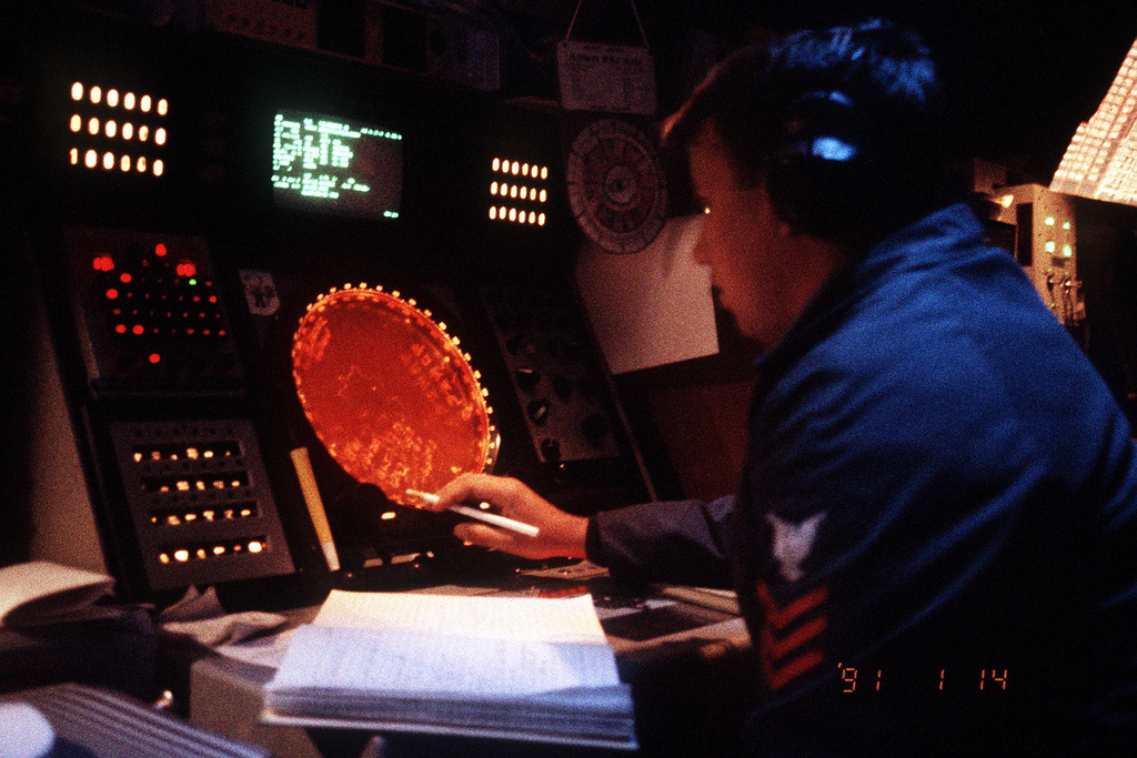 An air intercept controller monitors a radar screen in the combat information center aboard the guided missile cruiser USS BUNKER HILL (CG-52) during Operation Desert Shield