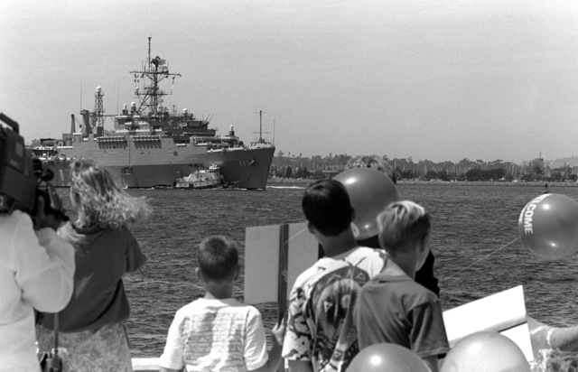 A crowd watches from the pier as a commercial harbor tug escorts the miscellaneous flagship USS CORONADO (AGF-11), flagship for commander, Third Fleet, toward a pier at Naval Station, North Island. The CORONADO has arrived at its new home port after spending almost 20 years in Hawaii