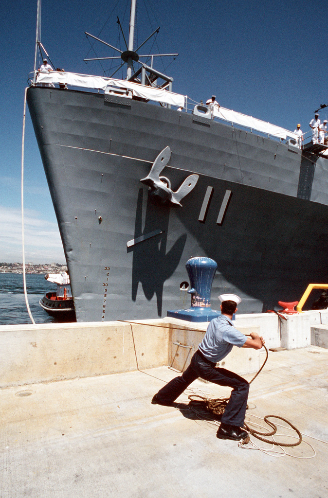 A line handler pulls on a mooring cable as the miscellaneous flagship USS CORONADO (AGF-11) is tied up in port at Naval Air Station, North Island, San Diego. The CORONADO, flagship for Commander, Third Fleet, will be arriving at its new home port after being stationed in Hawaii for almost 20 years