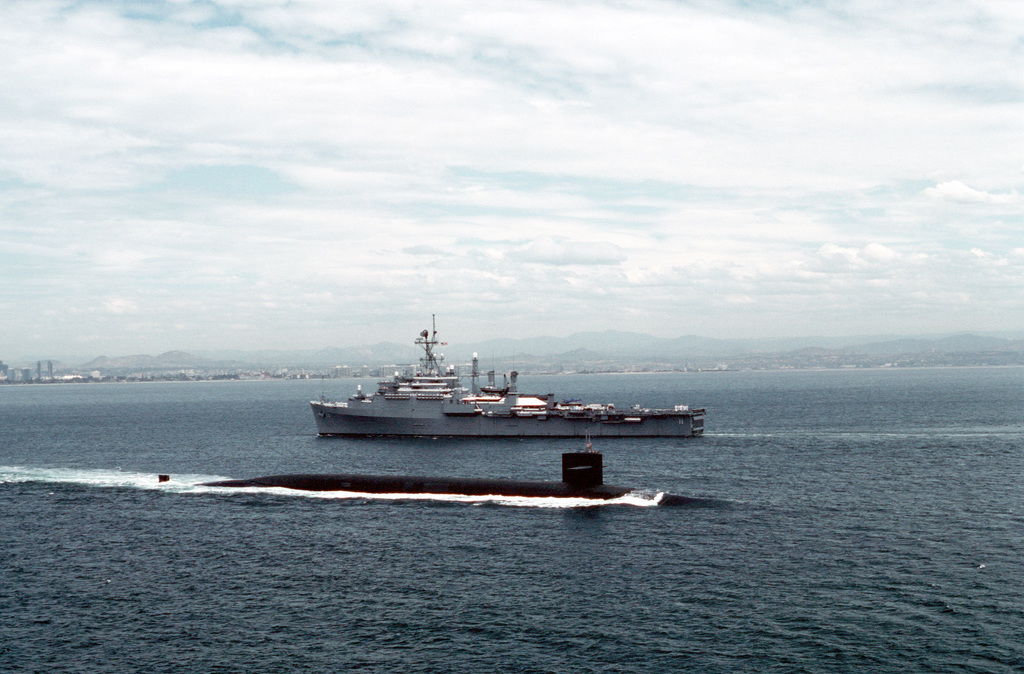 An Ohio class submarine travels out to sea as the miscellaneous flagship USS CORONADO (AGF-11) approaches Naval Air Station, North Island, San Diego. The CORONADO, flagship for Commander, Third Fleet, will be arriving at its new home port after being stationed in Hawaii for almost 20 years