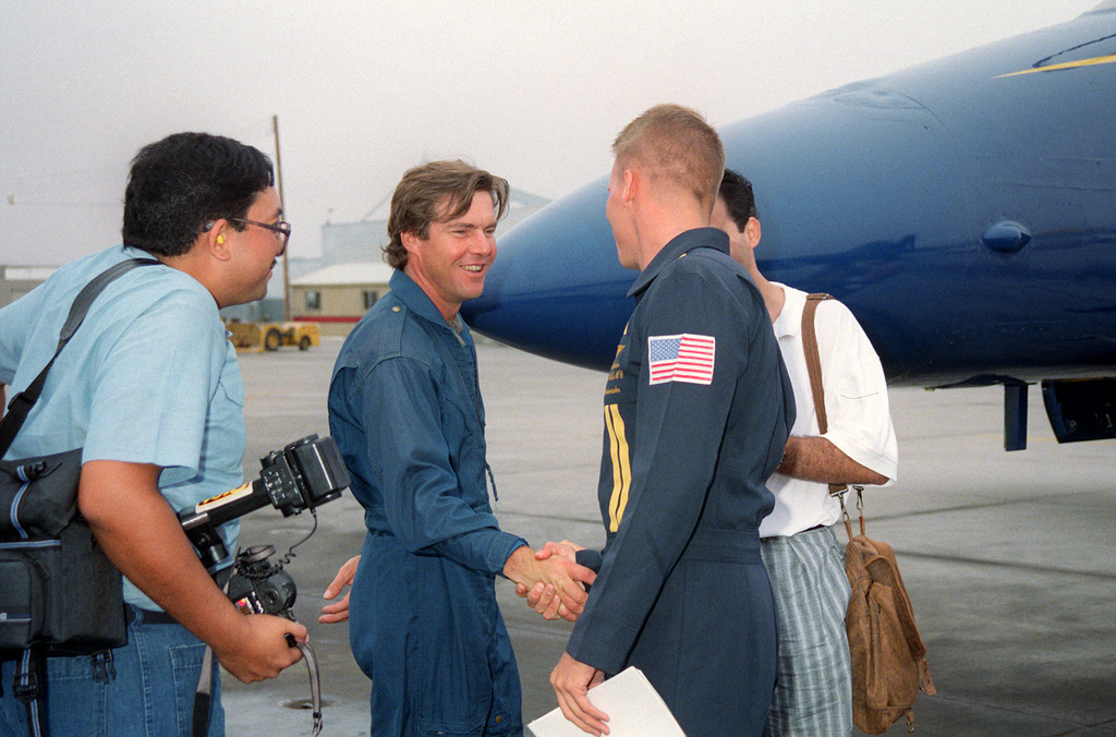 Actor Dennis Quaid gets a handshake from a ground crew member as he approaches the F/A-18 Hornet for his VIP flight with the US Navy (USN) Blue Angels