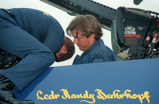 Ground crew member sets the radio channels in the cockpit of the US Navy (USN) Blue Angels F/A-18 Hornet for actor Dennis Quaid as he prepares for his VIP flight