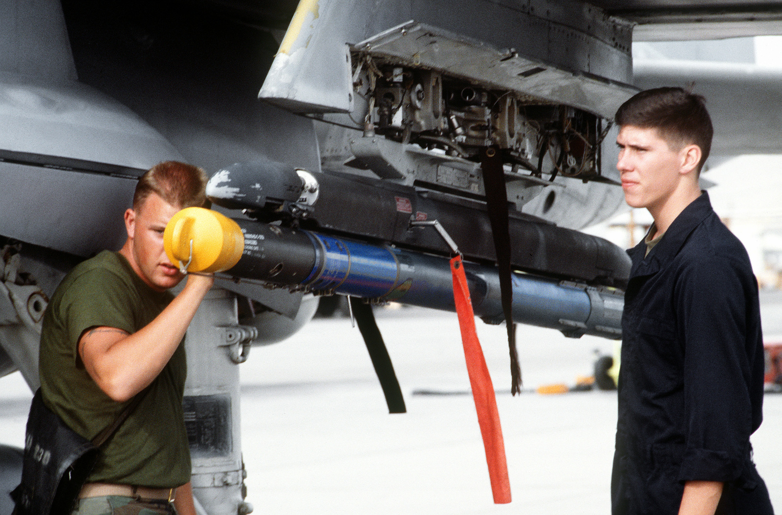 Members of Marine Attack Squadron 224 (VMA-224) inspect an AIM-9 Sidewinder missile mounted on the pylon of an A-6E Intruder aircraft. VMA-224, stationed at MCAS, Cherry Point, N.C., is on a two-week deployment to MCAS, Yuma