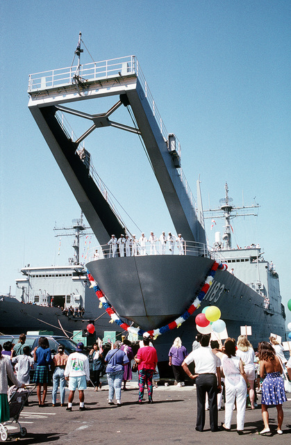 A garland decorates the bow of the tank landing ship USS PEORIA (LST-1183) as family and friends of crew members wait for loved ones to disembark from the vessel following its arrival in port. The PEORIA, along with other ships of Commander, Amphibious Squadron 1, has returned from the Persian Gulf area where it was deployed during Operation Desert Storm