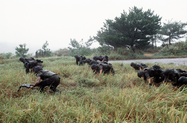 M-2 .50-caliber machine gun teams of the 2nd Battalion, 3rd Marine Regiment, 1ST Marine Brigade, prepare to advance across a field during a training exercise at the Central Training Area (CTA)