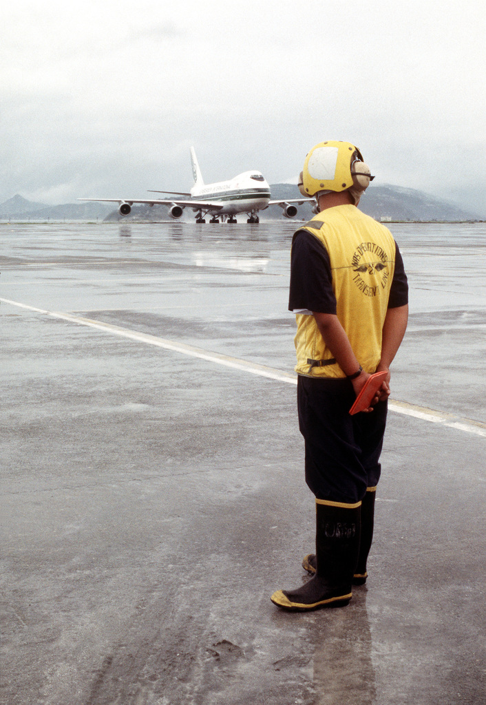 A member of the air station's operations department stands by to direct a chartered airliner as it taxis after landing. Aboard the airliner are dependents who had been evacuated from the air station and the nearby Subic Bay naval station during the eruption of Mount Pinatubo