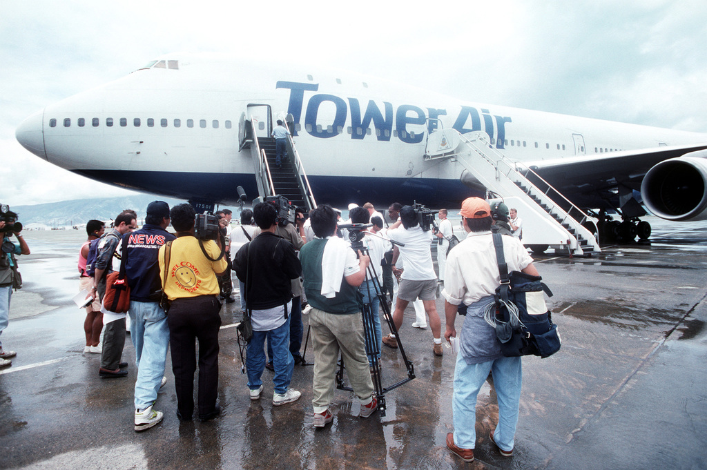 Members of the media film a Boeing 747 commercial aircraft after its arrival at the station. The aircraft is transporting family members of military personnel who are returning to the area after spending two months in the United States as part of Operation Fiery Vigil, the evacuation of military dependents following the volcanic eruption of Mount Pinatubo