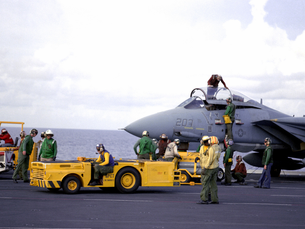 A flight deck crew member positions an MD-3A tow tractor near a Fighter Squadron 32 (VF-32) F-14A Tomcat aircraft on the flight deck of the aircraft carrier USS KITTY HAWK (CV-63)