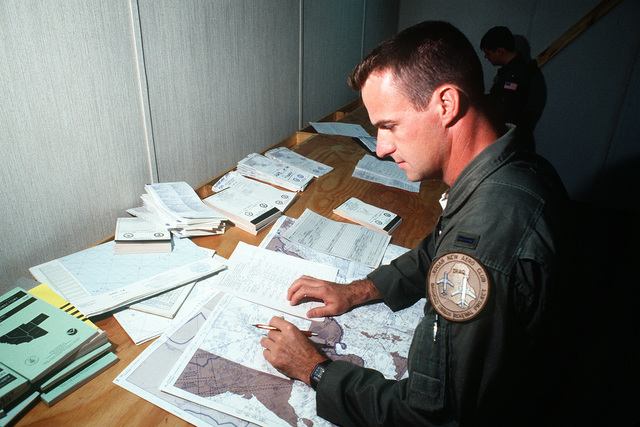 1ST LT. Mike Mathews, co-pilot of a KC-10A Extender aircraft, prepares for a Military Airlift Command channel cargo mission in the base operations center. LT. Mathews is a member of the 6th Air Refueling Squadron, 22nd Air Refueling Wing, March Air Force Base, California
