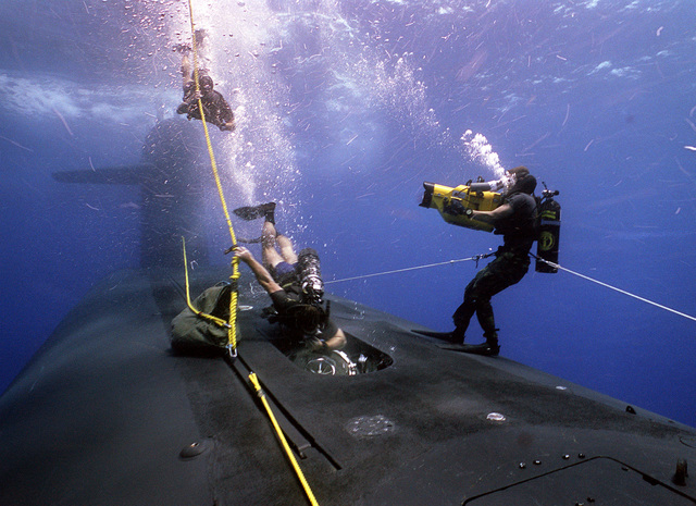 A member of a Navy sea-air-land (SEAL) team descends along a line as another SEAL enters the hull of the submerged nuclear-powered strategic missile submarine USS WOODROW WILSON (SSBN 624) during lock-out procedures off the coast of Puerto Rico. The maneuvers are being videotaped by a photographer's mate/diver.