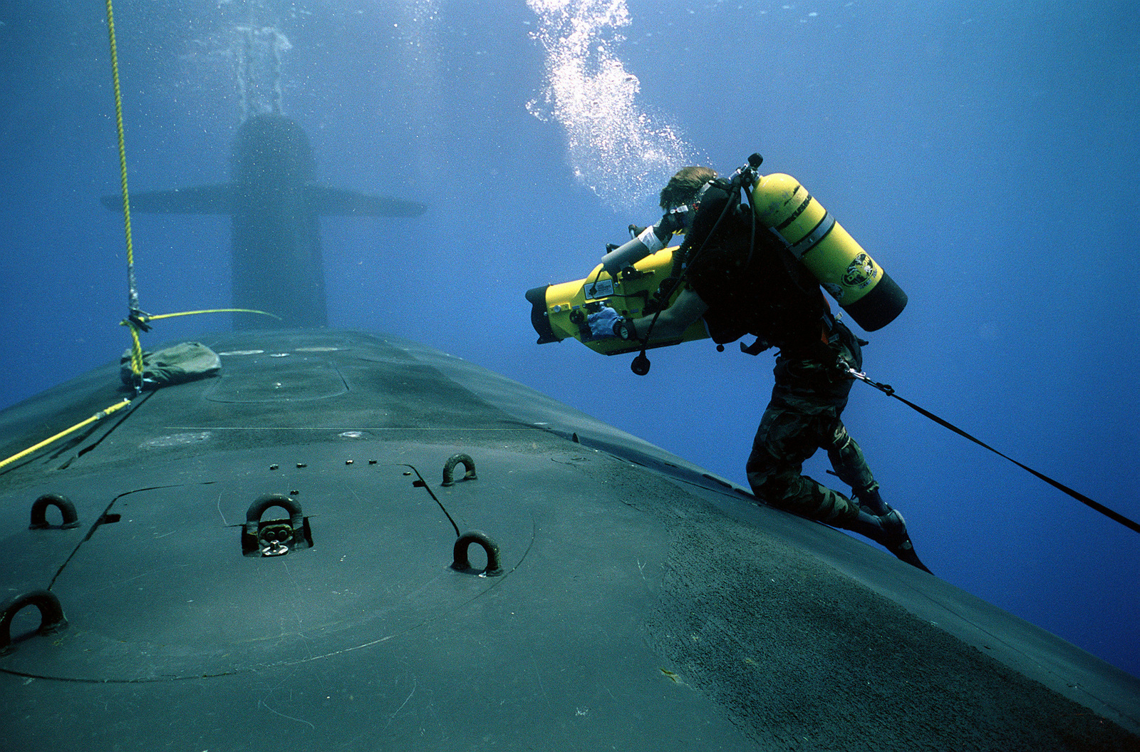 A photographer's mate/diver aims his camera at a hatch in the forward hull of the submerged nucelar-powered strategic missile submarine USS WOODROW WILSON (SSBN-624) while waiting for a Navy sea-air-land (SEAL) team member of the SEAL team as they practice entering and exiting the submarine during lock-out procedures off the coast of Puerto Rico.