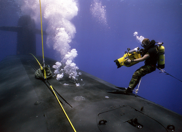 A photographer's mate/diver aims his video camera at a hatch in the forward hull of the submerged nuclear-powered strategic missile submarine USS WOODROW WILSON (SSBN 624) while waiting for a Navy sea-air-land (SEAL) team member to emerge. The cameraman is on hand to film the SEAL team members entering and exiting the vessel during lock-out procedures off the coast of Puerto Rico.