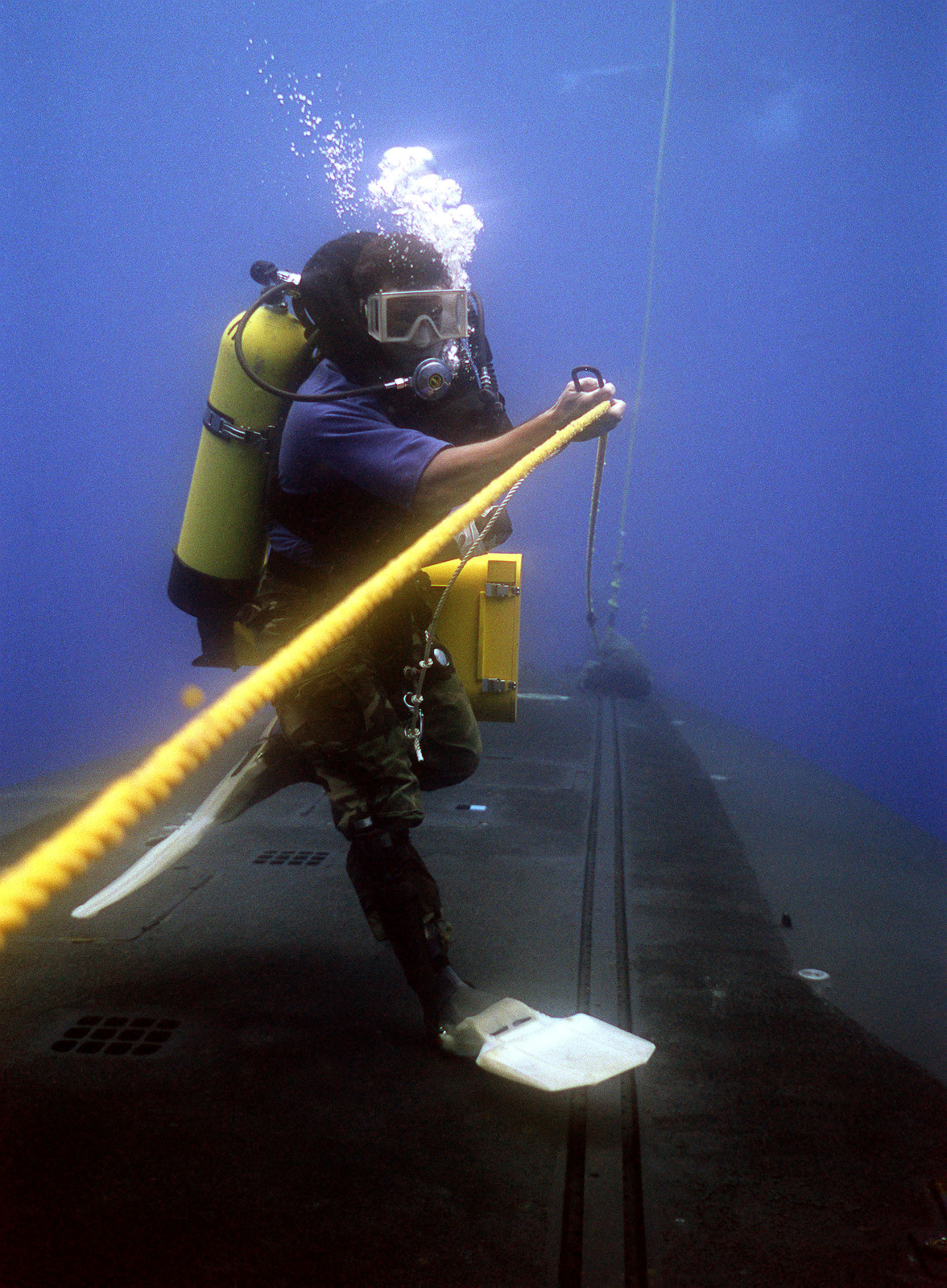 A photographer's mate/diver attaches his harness to a line rigged along the submerged hull of the nuclear-powered strategic missile submarine USS WOODROW WILSON (SSBN 624). The cameraman is preparing to videotape members of a Navy sea-air-land SEAL team as they practice entering and exiting the submarine during lock-out procedures off the coast of Puerto Rico.