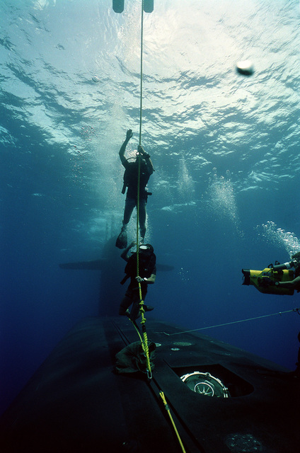 A photographer's mate/diver films members of a Navy sea-air-land (SEAL) team as they prepare to surface after taking part in lock-out procedures aboard the nuclear-powered strategic missile submarine USS WOODROW WILSON (SSBN-624) off the coast of Puerto Rico.