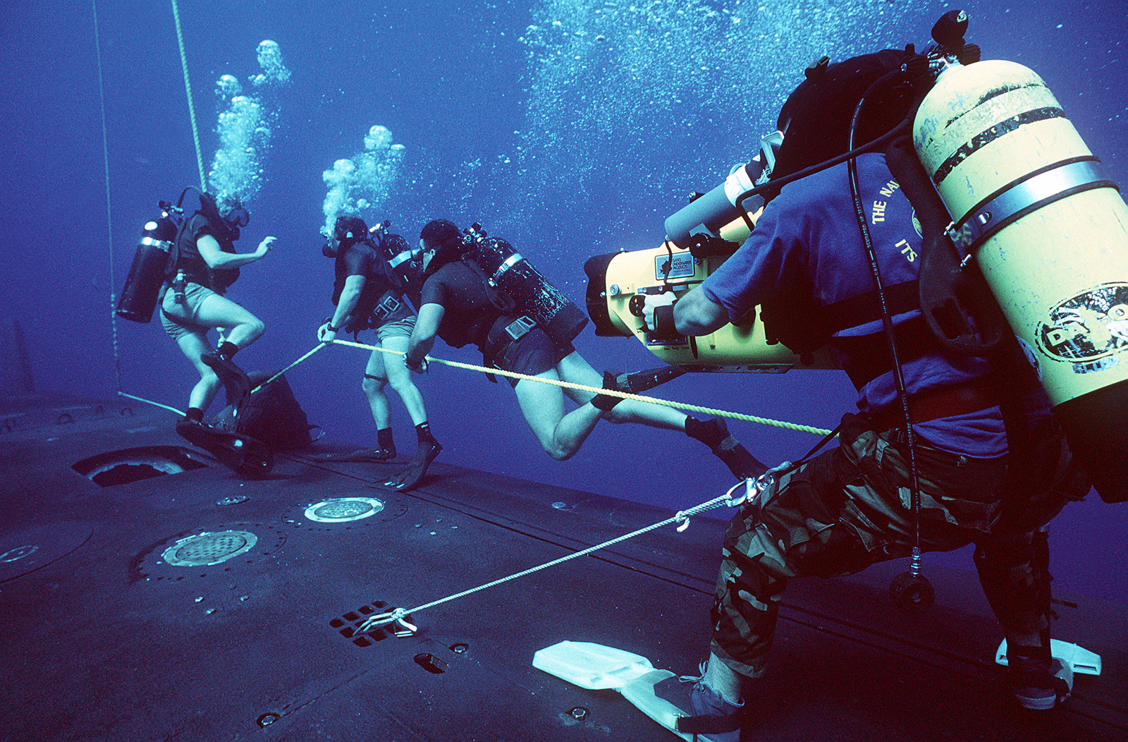 A photographer's mate/diver films the manuevers as members of a Navy Sea-Air-Land (SEAL) team swims along a line rigged to the hull of the submerged nuclear-powered strategic missile submarine USS WOODROW WILSON (SSBN-624) during lock-out procedures off the coast of Puerto Rico