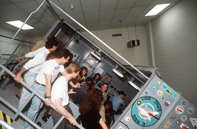 Civilian visitors experience the sensation of a submarine dive in a dive trainer