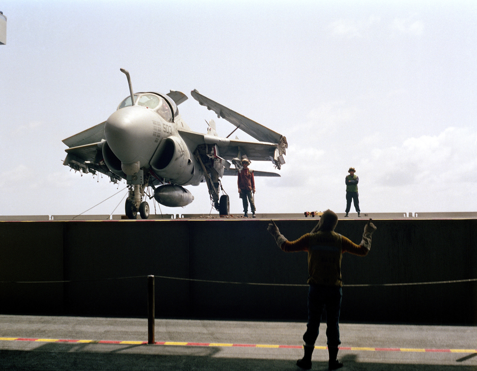 A crew member on an elevator signals to flight deck crew members as they stand beside as A-6E Intruder aircraft during a general quarters drill aboard the aircraft carrier USS KITTY HAWK (CV 63)