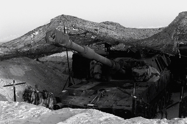 An M-109A1 self-propelled 155mm howitzer sits in a gun pit beneath a camouflage net during Operation Desert Shield. The howitzer is assigned to 5th Battalion, 11th Marines.