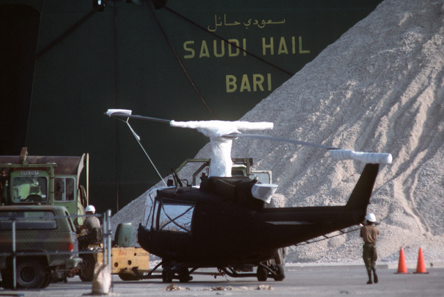 A soldier from the 1181st Transportation Terminal Unit holds the tail of a UH-1H Iroquois helicopter as it is pulled across the pier during loading operations at Blount Island Terminal. Helicopters and support equipment of the 101st Airborne Division (Air Assault) are being loaded aboard the Saudi Hail for transport to the Persian Gulf region for Operation Desert Shield