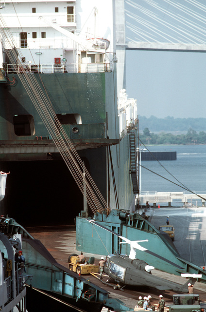 A tow tractor pulls a UH-1H Iroquois helicopter up the stern ramp of the Saudi Arabian roll-on/roll-off cargo ship SAUDI HAIL during loading operations at Blount Island Terminal. Helicopters and support equipment of the 101st Airborne Division (Air Assault) are being loaded aboard the Saudi Hail for transport to the Persian Gulf region for Operation Desert Shield
