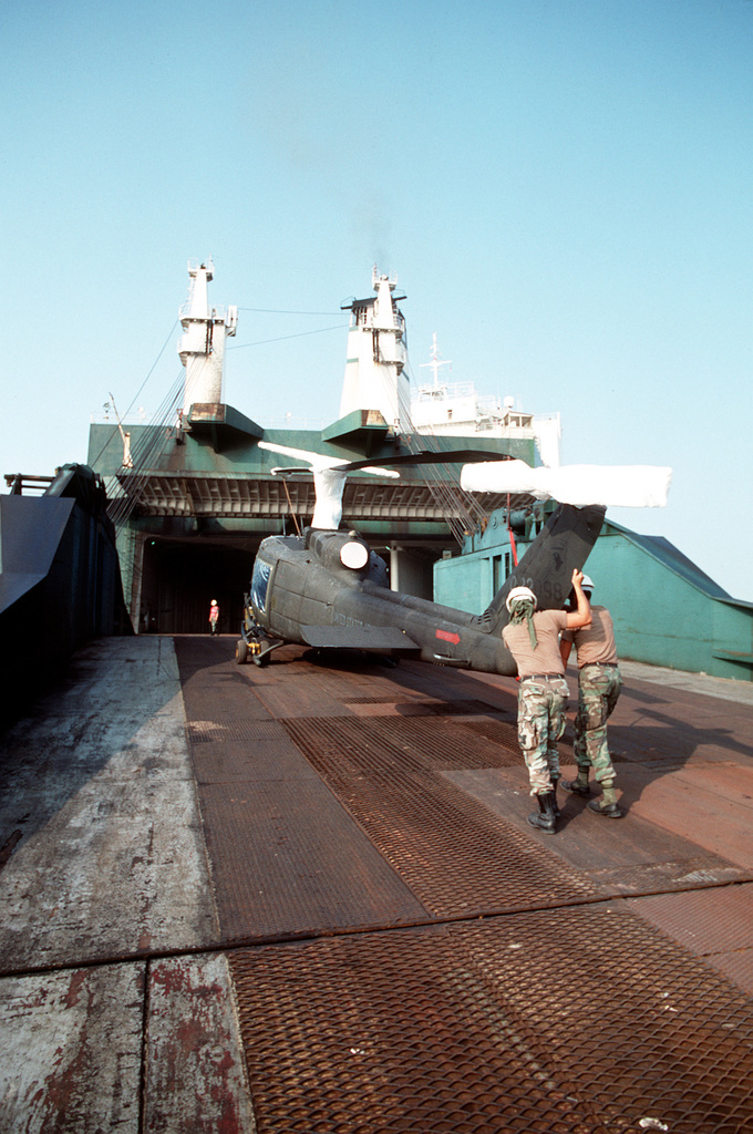 Two soldiers from the 1181st Transportation Terminal Unit hold up the tail of a UH-1H Iroquois helicopter as it is towed onto the Saudi Arabian roll-on/roll-off cargo ship SAUDI HAIL during loading operations at Blount Island Terminal. Helicopters and support equipment of the 101st Airborne Division (Air Assault) are being loaded aboard the Saudi Hail for transport to the Persian Gulf region for Operation Desert Shield