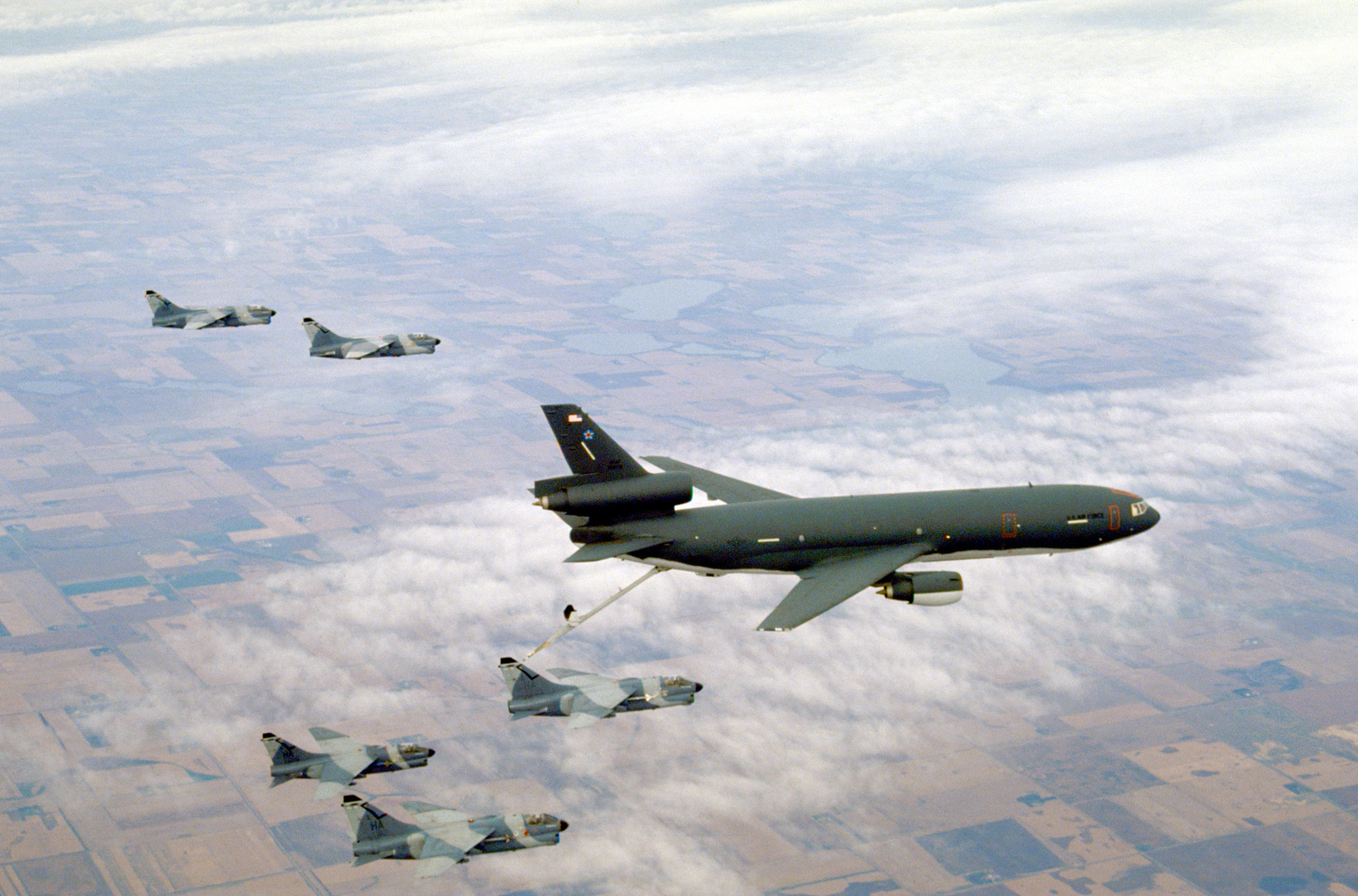 A 185th Tactical Fighter Group (185th TFG) A-7 Corsair II aircraft from the Air National Guard lines up for refueling from a 6th Aerial Refueling Squadron KC-10A Extender aircraft during Proud Visitor, a Headquarters, Strategic Air Command exercise. Other 185th TFG Corsairs fly in formation as they await refueling.