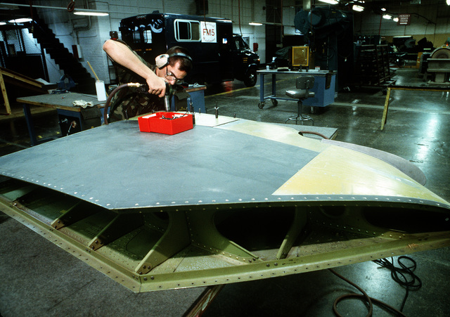 A1C Ken Chambers, a structural maintenance specialist with the 22nd Consolidated Aircraft Maintenance Squadron, attaches panels to a wing section of a Strategic Air Command KC-10A Extender aircraft.