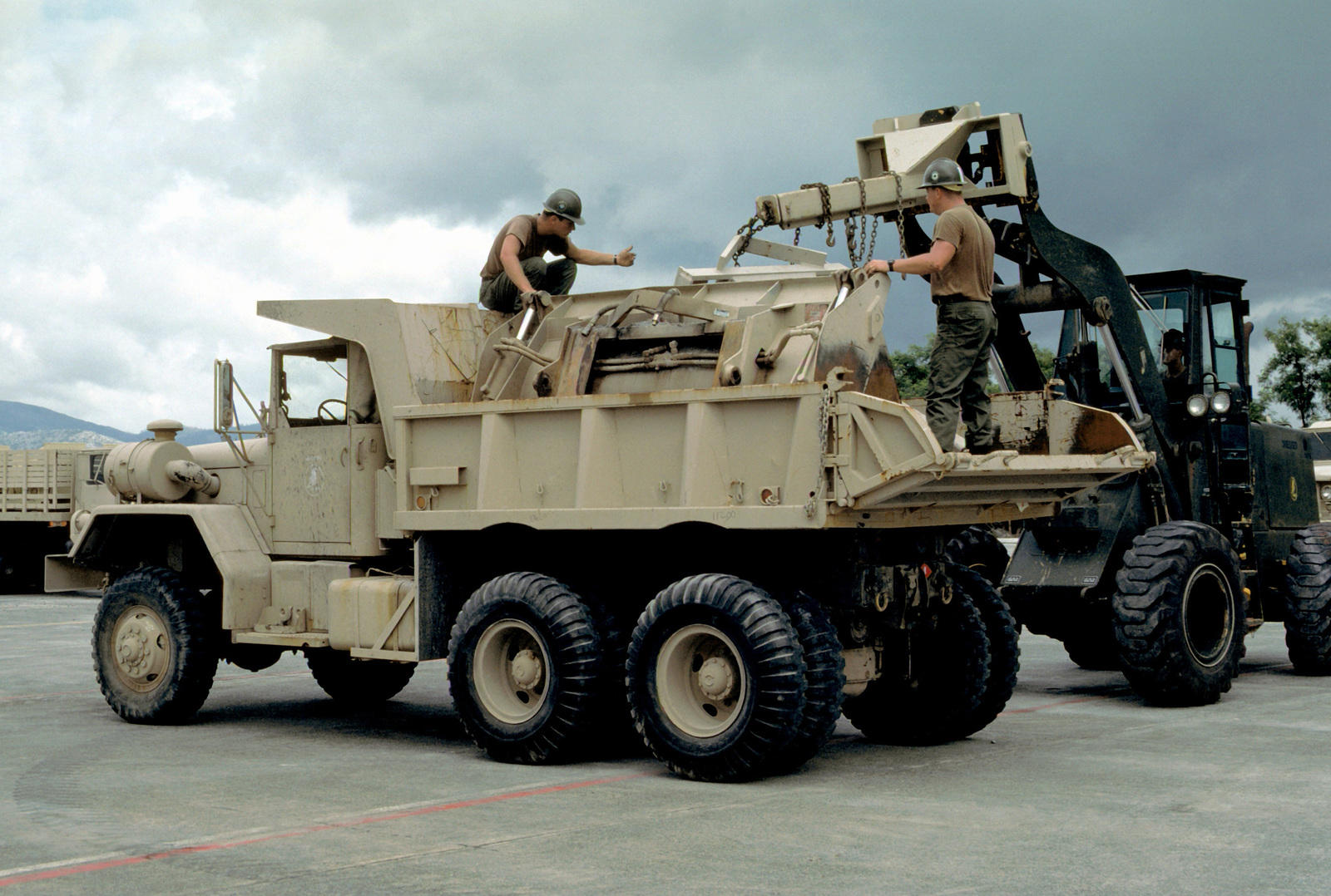 Two Seabees from Naval Mobile Construction Battalion 4 (NMCB-4) guide a forklift operator as he lowers a piece of equipment into the bed of an M-817 5-ton dump truck. NMCB-4 is preparing to leave Cubi Point after helping to clean up the volcanic ash from Mount Pinatubo that covered the area and caused some buildings to collapse