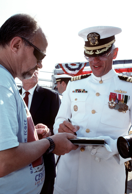 CAPT Conrad van der Schroeff, commanding officer of the battleship USS WISCONSIN (BB-64), signs autographs for crowd members following the ship's decommissioning ceremony