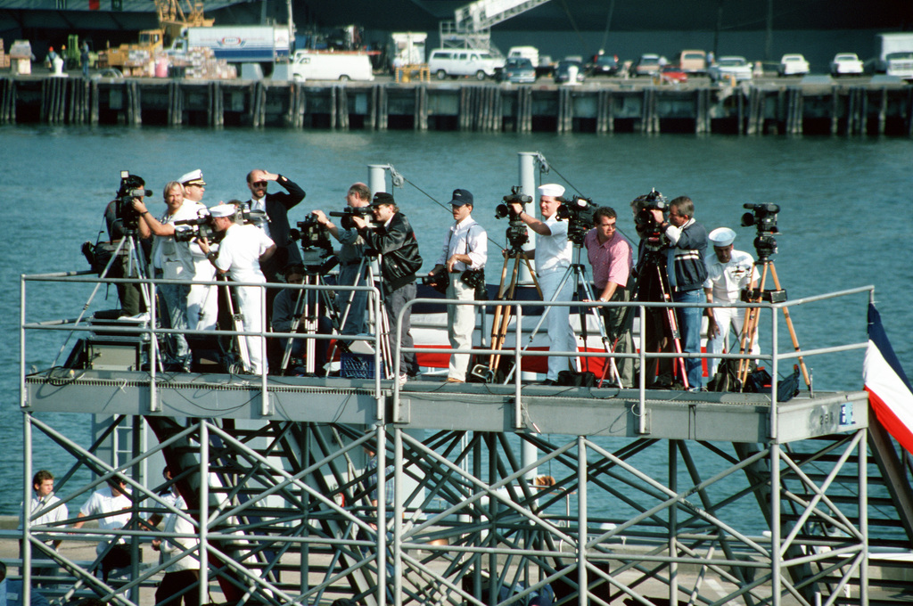 Navy and civilian journalists stand on a platform as they film the decommissioning ceremony for the battleship USS WISCONSIN (BB-64). The ceremony marks the end of the WISCONSIN's third period in commission, which began on October 22, 1988