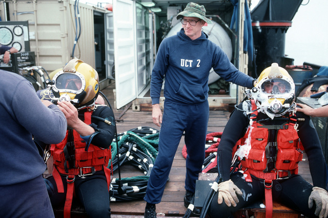 CHIEF Hospital Corpsman/Diver Betsill of Underwater Construction Team ( (UCT-2) assists and inspects divers wearing Mark 21 surface-supplied diving equipment before they enter the water. UCT-2, based out of Port Hueneme, California, is repairing underwater cables off the coast of the island