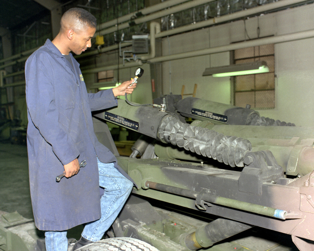 Darrin Moore tests part of the recoil mechanism of an M-198 155mm howitzer at the Rock Island Arsenal