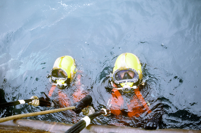 Divers from Underwater Construction Team 2 (UCT-2) of Port Hueneme, California, wearing Mark 21 surface-supplied diving suits, are ready to go to work on the ocean floor. UCT-2 is repairing underwater cables off the coast of the island. Exact Date Shot Unknown